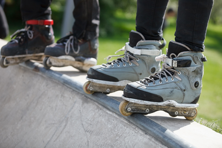 blading: Feet of rollerskaters wearing aggressive inline skates standing on top of concrete ramp in outdoor skate park. Stock Photo
