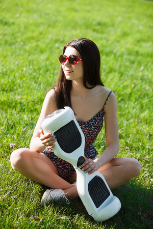 hover: Young brunette girl with electrical mini hover board scooter in green park. Stock Photo