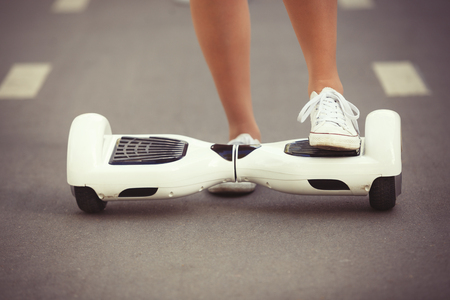 hover: Feet of girl riding electric mini hover board scooter outdoors in park. Ecological city transportation on battery power, produces no air pollution to atmosphere