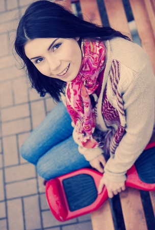 hover: Young white brunette woman holding modern red electric mini hover board scooter in hands sitting on bench. Stock Photo