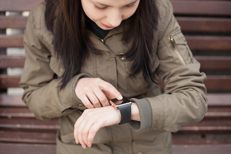 parka: Young hipster girl in parka coat using her smart watch.