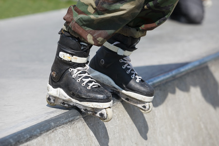 skate park: Feet of roller skater wearing aggressive inline skates grinding on concrete ramp in outdoor skate park. Stock Photo