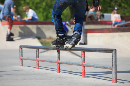 skate park: Feet of roller skater in aggressive inline skates grinding a rail in outdoor skate park. Stock Photo