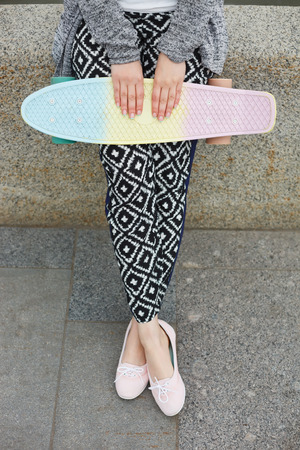 pink cruiser: Legs of young woman in boho style clothes holding short penny cruiser skateboard outdoors at day. Stock Photo