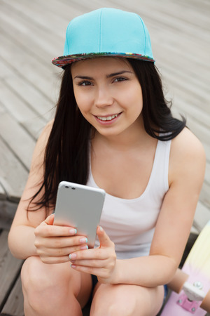 communicable: young brunette girl using big phablet smartphone with dual rear camera with a happy smile. Stock Photo