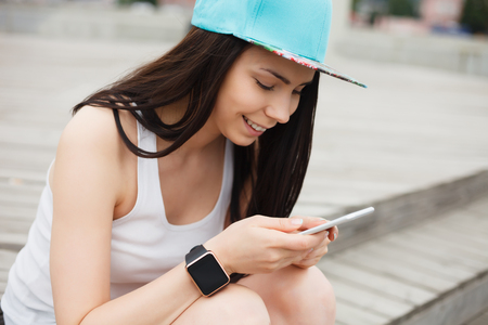 communicative: Attractive white brunette girl using her phablet smartphone.