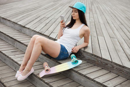 dual: Young white brunette girl using her modern smart phone with dual camera while leaning on the bench outdoors with her cruiser penny skateboard. Stock Photo