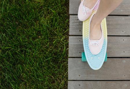 pied jeune fille: Pieds de fille d'équitation moderne penny courte cruiser planche à roulettes dans les chaussures roses. Banque d'images