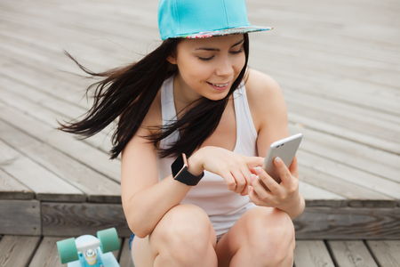 communicative: Attractive white brunette girl using her phablet smartphone with dual rear camera. Stock Photo