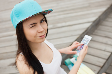 communicative: Cute young white brunette girl using big smartphone with wink in her eyes. Stock Photo