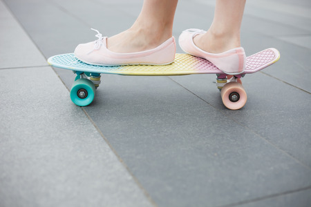 pink cruiser: Feet of girl riding modern short cruiser penny skateboard in pink shoes.