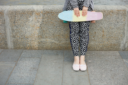 pink cruiser: Legs of girl in boho style clothes holding short cruiser penny skateboard outdoors at day.