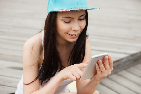 communicative: Attractive white brunette woman using her phablet smartphone with dual rear camera smiling.