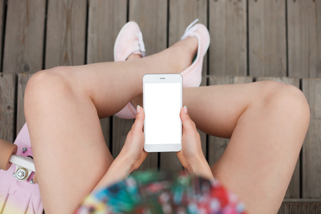 communicable: Young girl using big white phablet smartphone with blank white screen.