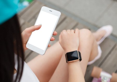 communicative: Young girl using big white phablet smartphone with blank white screen with smart watch on the other hand.