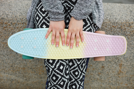 pink cruiser: Hands of girl in boho style clothes holding short penny cruiser skate board outdoors at day. Stock Photo