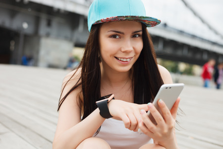communicable: Attractive white brunette girl using her phablet smartphone with dual rear camera. Stock Photo