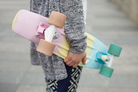 pink cruiser: Hands of young woman in boho style clothes holding short cruiser pennyboard outdoors at day. Popular colorful skateboarding deck and trendy fashionable clothing
