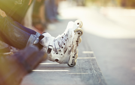 blader: Feet of rollerskate wearing aggressive inline skates sitting on a ledge wtih crowd in outdoor skate park. Extreme sports athlete wearing roller blades for tricks and grinds
