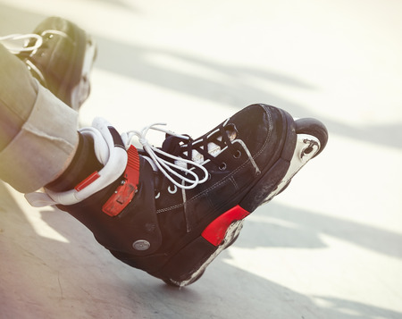 blader: Feet of rollerskate wearing aggressive inline skates sitting on a concrete ramp in outdoor skate park. Extreme sports athlete wearing roller blades for tricks and grinds