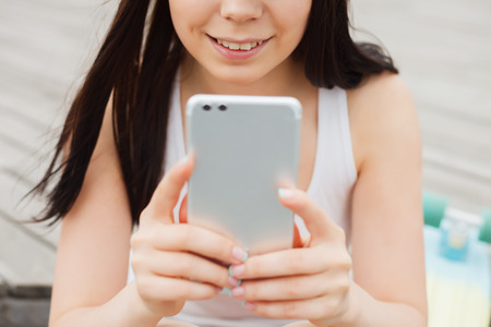 communicable: Smiling young brunette woman using big phablet smartphone with dual rear camera with a happy smile. Modern technology, cute model Stock Photo