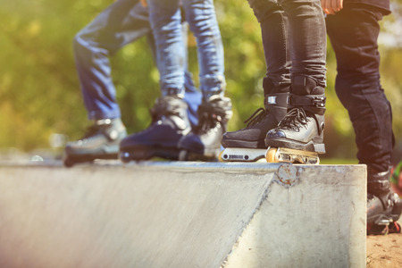 blader: Feet of rollerskater wearing aggressive inline skates standing on top of concrete ramp in outdoor skate park. Extreme sports athlete wearing roller blades for tricks and grinds