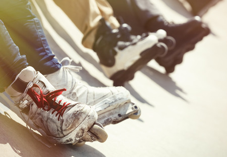 blader: Feet of rollerbladers team wearing aggressive inline skates sitting on a concrete ramp in outdoor skatepark. Extreme sports athletes wearing roller blades for tricks and grinds