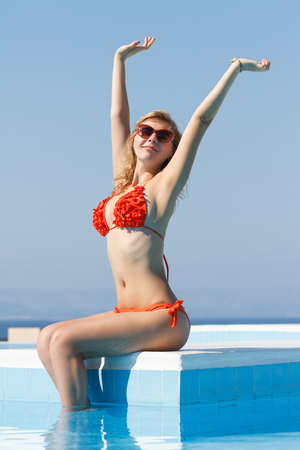 blondy: Happy young white blond woman sitting at the swimming pool with legs in water. Vibrant color, bright sun and attractive blondy woman. Happy facial expression Stock Photo