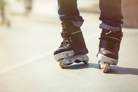 blader: Aggressive inline skates on rollerblader feet. Extreme sports athlete in concrete outdoor skate park. Focus on roller blades, professional model for tricks and grinds