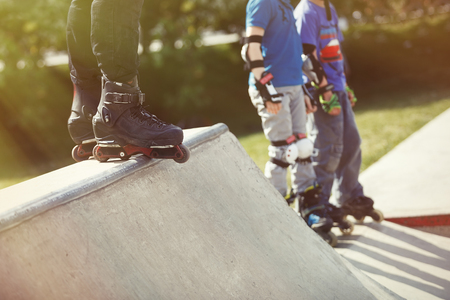 skate park: Feet of rollerskater wearing aggressive inline skates standing on top of concrete ramp in outdoor skate park. Extreme sports athlete wearing roller blades for tricks and grinds
