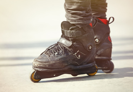 blading: Aggressive inline skates on rollerblader feet. Extreme sports athlete in concrete outdoor skate park. Focus on roller blades, professional model for tricks and grinds