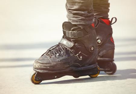inline agresivo patines en los pies rollerblader. Atleta de deportes extremos en la pista de patinaje al aire libre de hormigón. Centrarse en las láminas del rodillo, modelo profesional para los trucos y rutinas