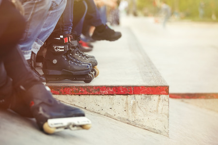 blader: Feet of rollerblader wearing aggressive inline skates sitting on a ledge wtih crowd in outdoor skate park. Extreme sports athlete wearing roller blades for tricks and grinds Stock Photo