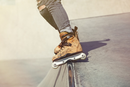 blader: Feet of rollerskater  wearing aggressive inline skates grinding on concrete ramp in outdoor skate park. Extreme sports athlete wearing roller blades for tricks and grinds