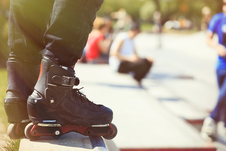 blading: Feet of rollerblader wearing aggressive inline skates standing on top of concrete ramp in outdoor skate park. Extreme sports athlete wearing roller blades for tricks and grinds Stock Photo