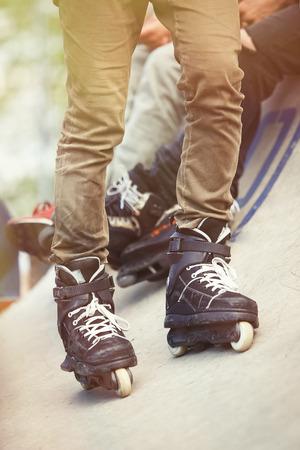 rollerskater: Aggressive inline skater on rollerskater  standing on ramp. Extreme sports athlete in concrete outdoor skate park. Focus on roller blades, professional model for tricks and grinds