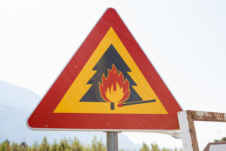 Be careful with forest fire while camping on vacation.Triangle road sign with fire flames and burning match warns young about danger of catastrophe.Hazardous area Stock Photo