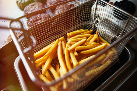 Delicious golden French fries frying on kitchen in cafe.Fast food restaurant background.Unhelathy but tasty junk foods.Fat oily potato sticks fried in basket.High level of cholesterol and saturated fats