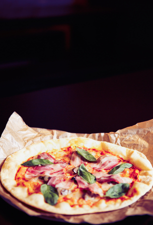 Natural Italian pizza dish served on decorative paper plate in fast food restaurant.Delicious natural ingredients on fresh baked dough.Basil leaves,slices ham and burned cheese with spices