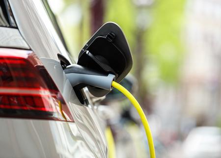 Laden Sie die Batterien des Elektroautos Moden auf dem Parkplatz mit gelbem Kabel. Laden Sie Ihr Fahrzeug mit Strom für eine neue Fahrt auf. Ökologischer Stadtverkehr ohne Luftverschmutzung Standard-Bild