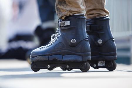 Agressieve inline rollerblader die grote zwarte skates draagt voor extreem skaten.Voeten van jonge atleet in inline blades trainen in skatepark buiten in de zomer