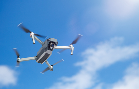 Modern aerial drone with propellers and wireless remote control flying high in the air filming high resolution landscape video with digital camera on stabilized gimbal head Stock Photo