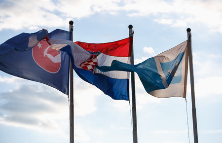 National flag of Crotia and Dalmatia region high on pole with bright blue sky on background.Traditional Croatian red,white and blue colors and symbols