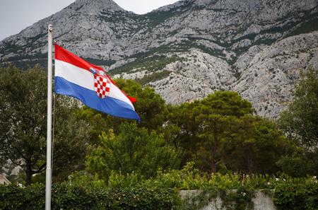 National Croatian flag high on metal pole with Biokovo Mountain park on background. Traditional symbol of Croatia