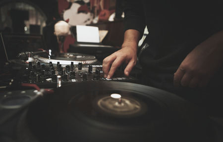 Professional dj plays music on vinyl records player turn table