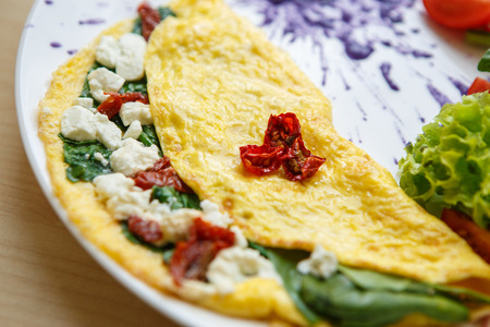 Delicious omelette for brunch in cafe.Tasty natural food with natural ingredients.Fried eggs,dryed tomato,spinach and Greek feta cheese served on white plate in restaurant