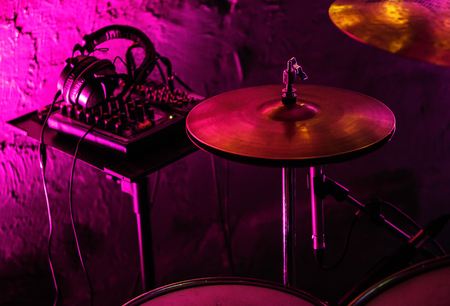 Professional drum kit cymbals & stereo headphones monitors on stage in bright magenta lights.Music hall audio equipment for rock concert.Drumset for drummer musician on nigthclub scene