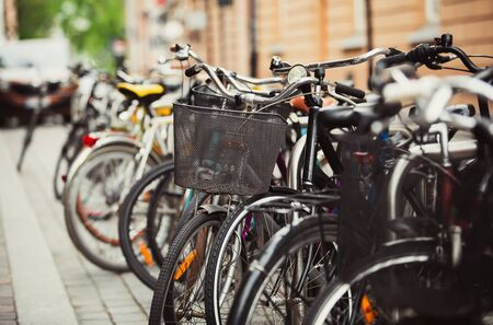 Many bicycles parked in European city parking lot in the street. Popular ecological urban transport for active people. Healthy transportation mode in Europe