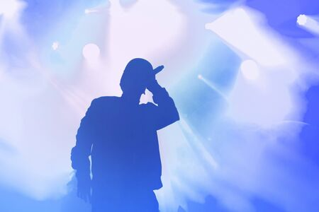 Young rap singer with mic in hand singing popular song in stage in bright blue lights.Hip hop artist performing live on scene in music hall.Youth entertainment event in nightclub.Professional vocalist Stock fotó