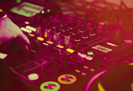 Edm party dj play musical tracks with modern sound mixer and turntables in bright red lights on stage in music hall.Professional disc jockey audio equipment in close up.Musician plays set